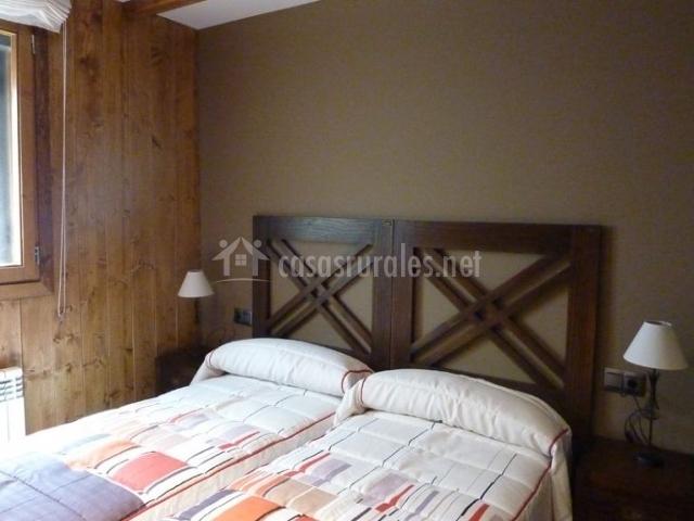 Dormitorio doble con ventana y paredes de madera