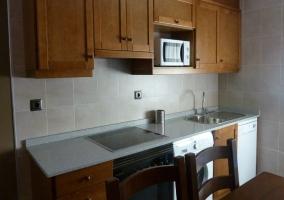 Cocina con vitro y una mesa de madera