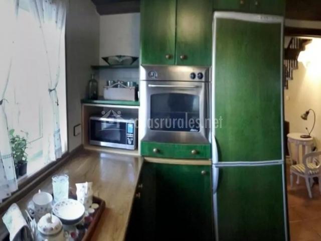 Cocina con armarios en color verde y ventana