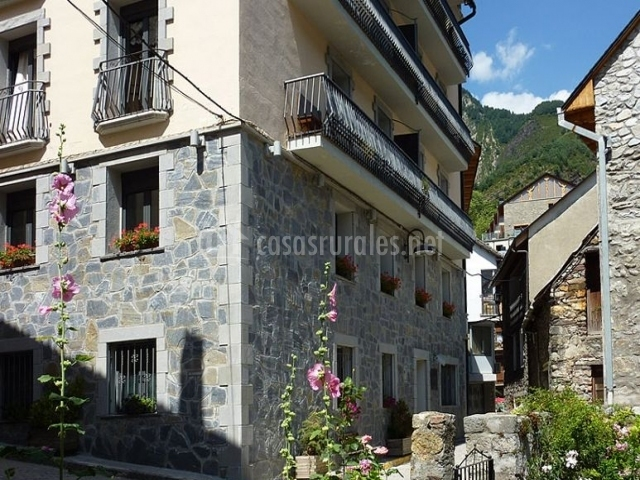Acceso a la vivienda con fachada en piedra y balcones