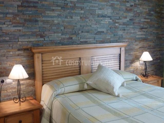 Dormitorio de matrimonio con colcha de cuadros y mesillas