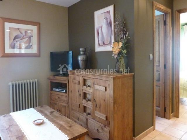 Sala de estar con la mesa en el centro y una tele