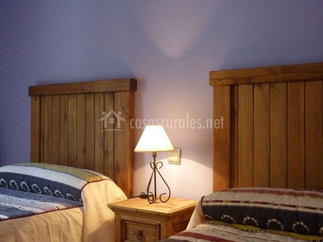 Dormitorio doble con una mesilla demadera entre sus camas