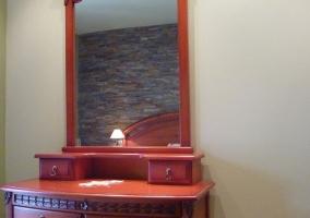 Dormitorio de matrimonio con mesillas de noche y mueble en madera