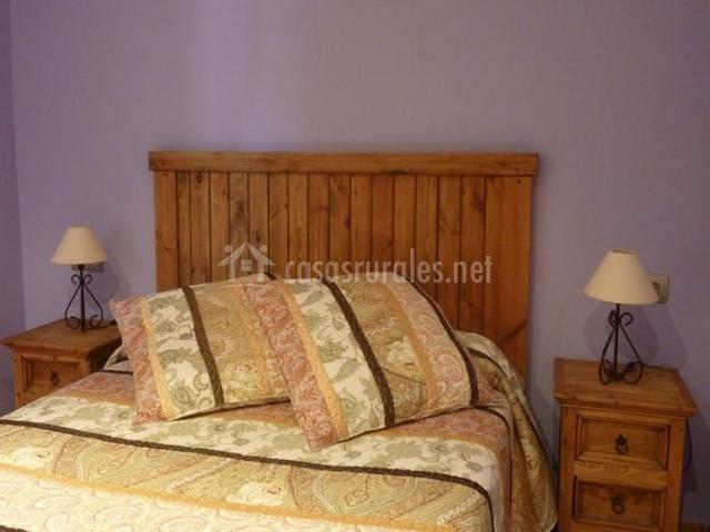 Dormitorio de matrimonio con cabecero en madera y mesillas