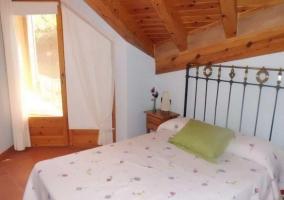 Dormitorio con techo abuhardillado y cuna