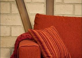 Sala de estar con sillones en rojo y mesa de comedor delante