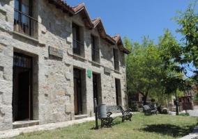 Acceso a los alojamientos con zonas verdes delante y bancos