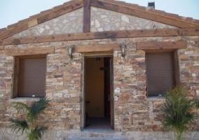 Acceso a la casa con fachada en piedra y plantas