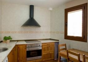 Cocina con mesa de madera y encimera en L