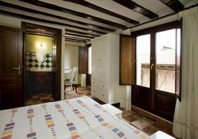 Dormitorio con un par de camas y aseo integrado