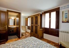 Dormitorio de matrimonio con cabecero de madera y aseo