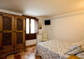 Dormitorio de matrimonio con cabecero de madera y televisor