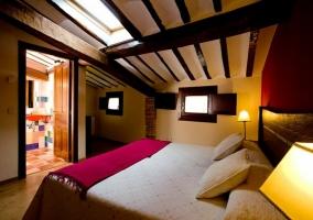 Dormitorio doble con frente en color rojo abuhardillado con aseo