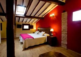 Dormitorio doble con frente en color rojo abuhardillado con tragaluz