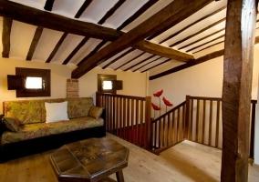 Dormitorio doble con frente en color rojo abuhardillado y sala de estar