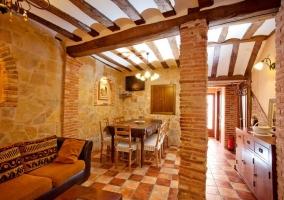 Sala de estar y comedor con paredes de piedra