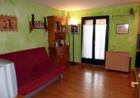 Sala de estar con paredes en verde y suelos de madera