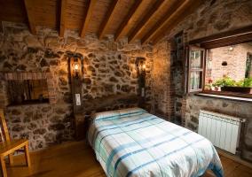 Dormitorio con cama de matrimonio y ventana a un lado