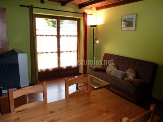 Sala de estar y paredes en verde con mesa de madera