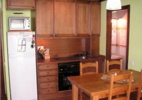 Cocina con la mesa de madera y armarios