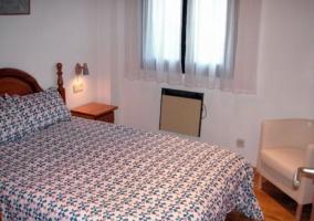 Dormitorio de matrimonio con cabecero de madera y cuadros