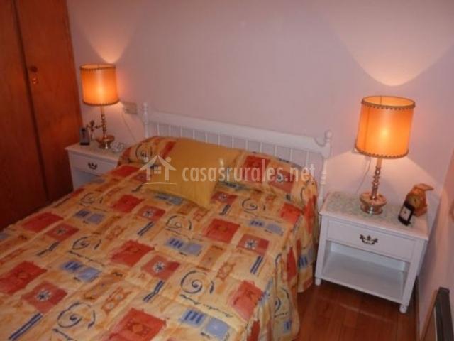 Dormitorio de matrimonio con suelo de madera y cabecero blanco