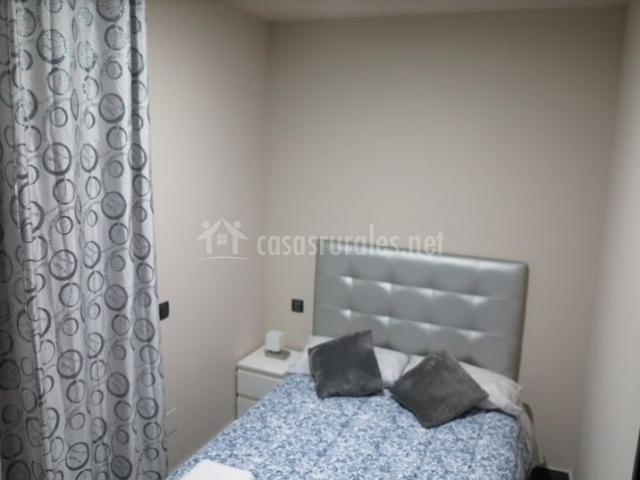 Dormitorio con cama amplia y detalles plateados
