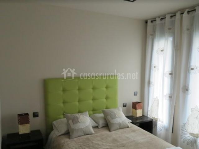 Dormitorio de matrimonio con cabecero acolchado y ventanas