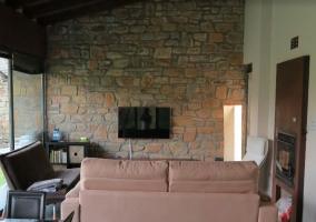 Sala de estar con paredes en piedra y sillones en tonos tierra
