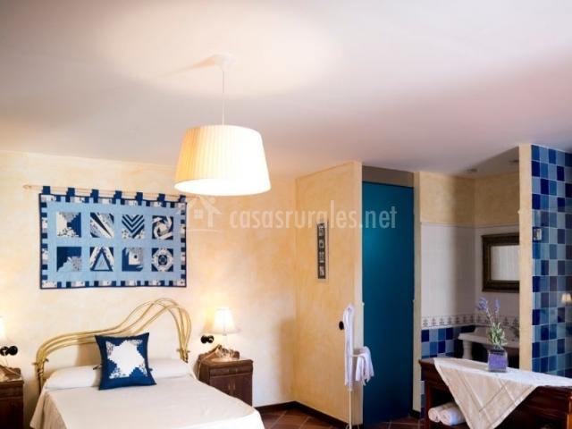 Dormitorio de matrimonio azul con su aseo con ducha al lado