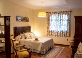 Dormitorio de matrimonio con un banco de madera