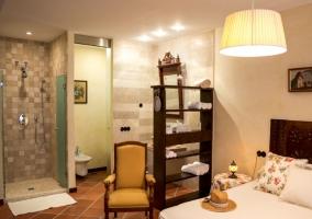 Dormitorio de matrimonio con un banco y aseo al lado con ducha