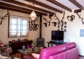 Sala de estar con sillones morados y una chimenea junto a la tele