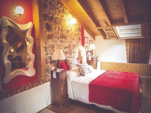 Dormitorio abuhardillado con paredes en piedra