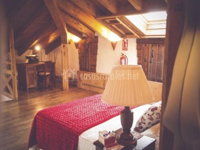 Dormitorio abuhardillado con su escritorio