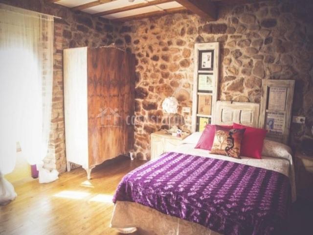 Dormitorio de matrimonio amplio y con mantas moradas