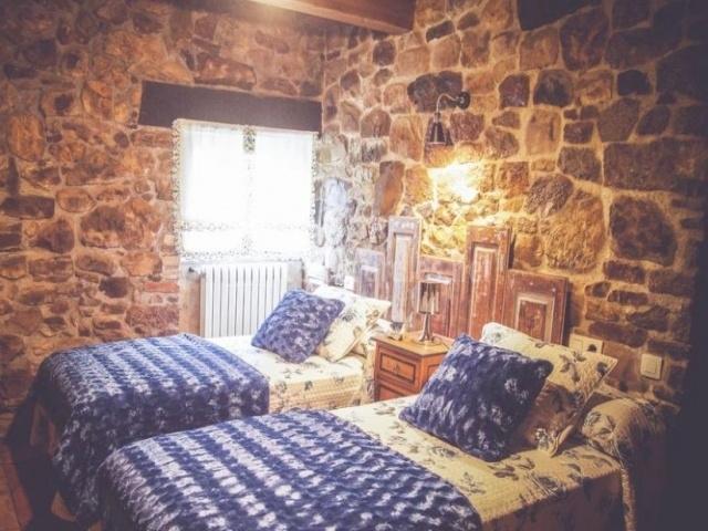 Dormitorio doble con mantas azules y paredes de piedra