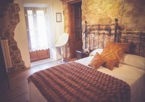 Dormitorio de matrimonio con cabeceros en forja y aseo