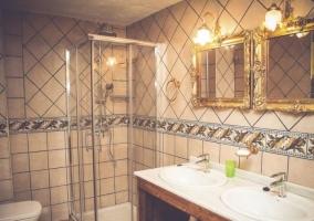 Dormitorio de matrimonio con cabeceros en forja y su aseo completo
