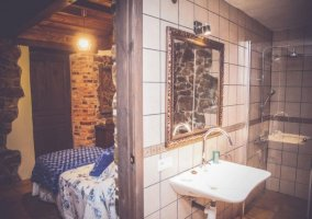 Dormitorio doble con mantas azules y su aseo con la ducha