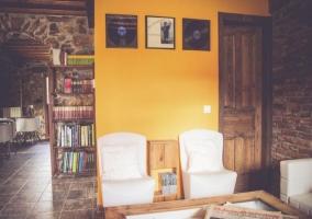 Sala de estar con mesa de madera y sillones blancos