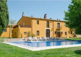 Acceso a la casa con piscina y fachada en amarillo