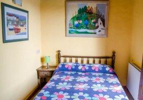 Dormitorio de matrimonio con colchas de flores