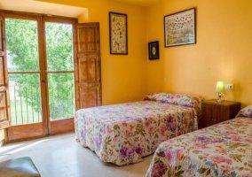 Dormitorio doble con colchas de flores y mesilla de madera