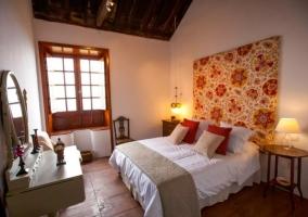 Dormitorio de matrimonio con cabecero tapizado con detalles en rojo