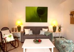 Sala de estar con cuadros en verde y mecedora