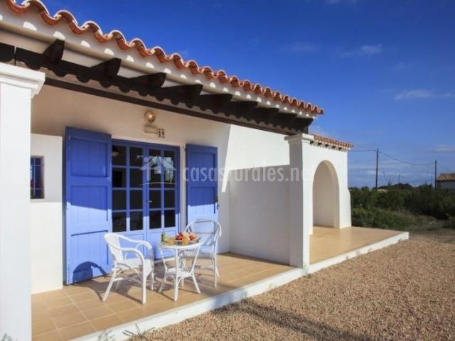 Acceso a la casa con porche equipado y puertas azules