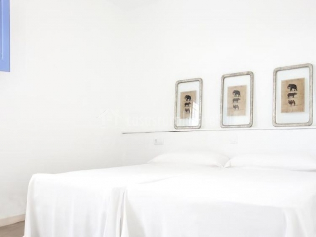 Dormitorio doble con cuadros sobre las camas