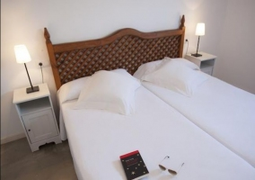 Dormitorio doble con cabecero de madera y mesillas
